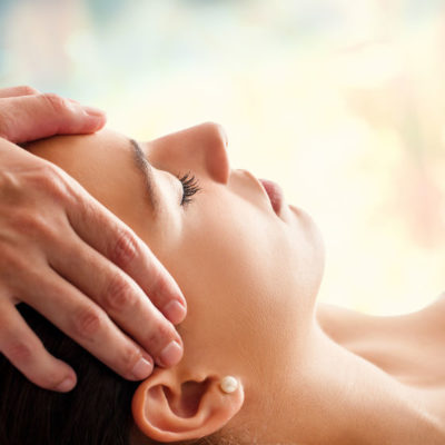 Close up head portrait of young woman having facial massage in spa. Therapist massaging woman's head against colorful background.