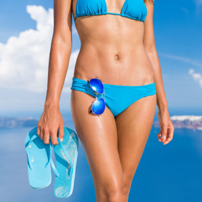 95189265 - sun beach bikini body woman with toned abs and slim legs tanning on vacation holding flip flops sandals and sunglasses accessories. fit stomach weight loss and cellulite free thighs skin care concept.