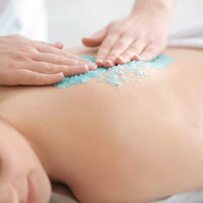 Beautiful young woman receiving scrub massage in spa salon, closeup